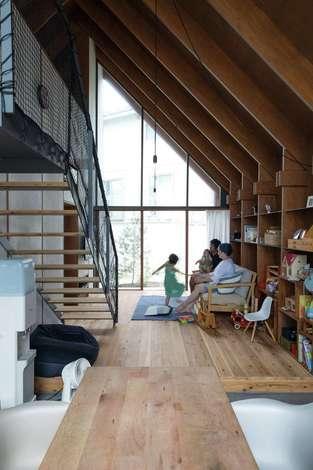 建杜 KENT(大栄工業)|大きな三角屋根の半分は吹き抜け。家の南北がガラス張りになっているため、朝、自然の光が目覚めを誘う。杉の無垢材とモルタル、アイアンを使った、裸足で過ごせる家は素材の経年変化も楽しみだ。壁面はすべて、構造体のパネルを活用したオープンシェルフになっている