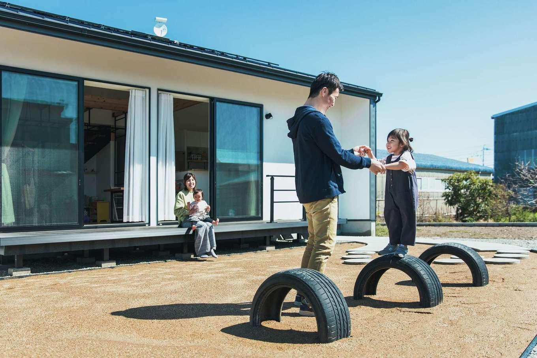 """ワンズホーム【デザイン住宅、子育て、建築家】庭はまさに""""運動場""""。タイヤを埋めた遊具や砂山がある"""