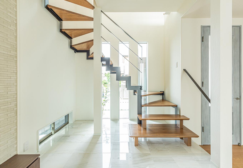 白タイルの床がスリット窓から入る光を反射する、高級感漂う階段コーナー。リビングから床を一段上げて空間を区切り、アイアンと木で制作したオリジナルの階段が美しく映える
