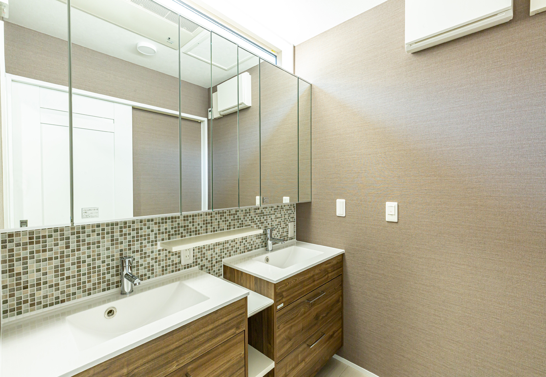 ゴージャスなツインボウルの洗面室。実は単品の洗面台を2つ並べ、間に収納棚を造作したもの。タイルと鏡で違和感なくつなげ、上部には間接照明も。使いやすさとかわいさを両立させた