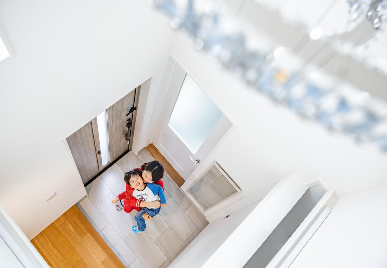 玄関は開放感のある吹き抜け空間。通常の動線のほか、靴やゴルフ用品、仕事の道具などを収納できるシューズクロークに内玄関を設け、家族はそこから出入りできる回遊動線も作った