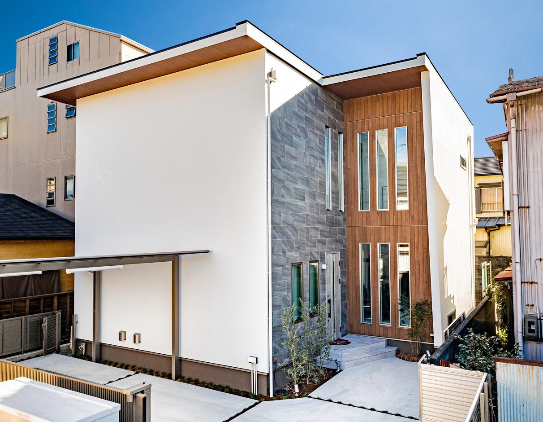土地が旗竿型のため、駐車場での切り返しがスムーズにできるように建物の形を工夫。玄関部分のみタイルと木目調の外壁に変え、スリット窓が高級感を演出する