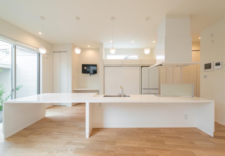 i.u.建築企画【デザイン住宅、建築家、ガレージ】造作のテーブルと既存のシステムキッチンを組み合わせたアイランドキッチンは、一体型のオーダーメイド品のように完成度の高い仕上がり。バックヤードの造作収納も白で統一