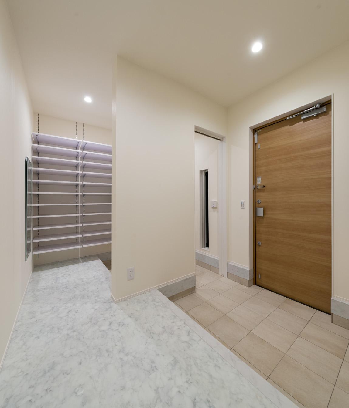i.u.建築企画【デザイン住宅、建築家、ガレージ】玄関には大容量のシューズクロークを併設。ホールの床には大理石調のフロアタイルを採用し、シンプルモダンにコーディネート