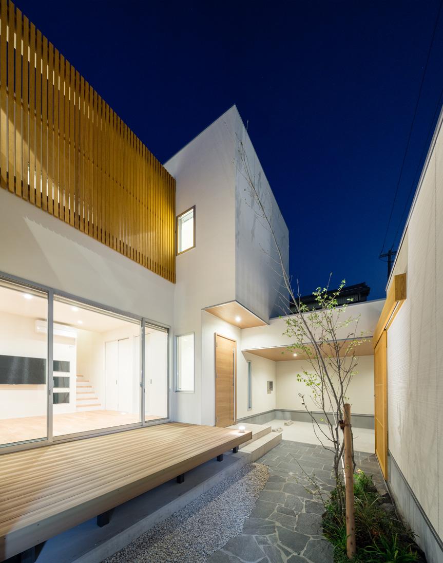 i.u.建築企画【デザイン住宅、建築家、ガレージ】室内窓から漏れる灯りが白壁をほんのりと照らし、情緒を醸し出す夜の中庭。ガレージからは雨天でも濡れずに玄関に行けるように設計されている。デザインに偏らず、機能性や性能もハイスペックなのが『i.u.建築企画』の住まいの特徴だ