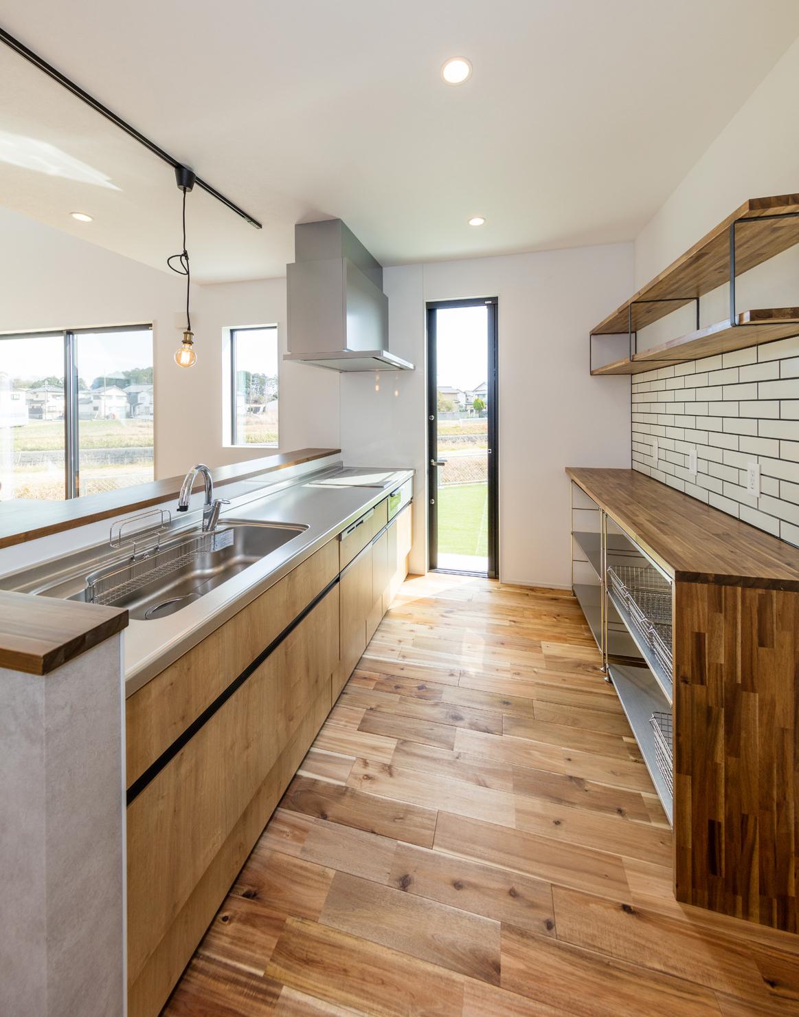 対面キッチンに立つと、LDKや庭を見渡せる。背面の壁はタイル張りにし、造作の収納を設けてある。上部のオープンラックにはお気に入りの器やキッチンアイテムを飾って、室内をオシャレに演出