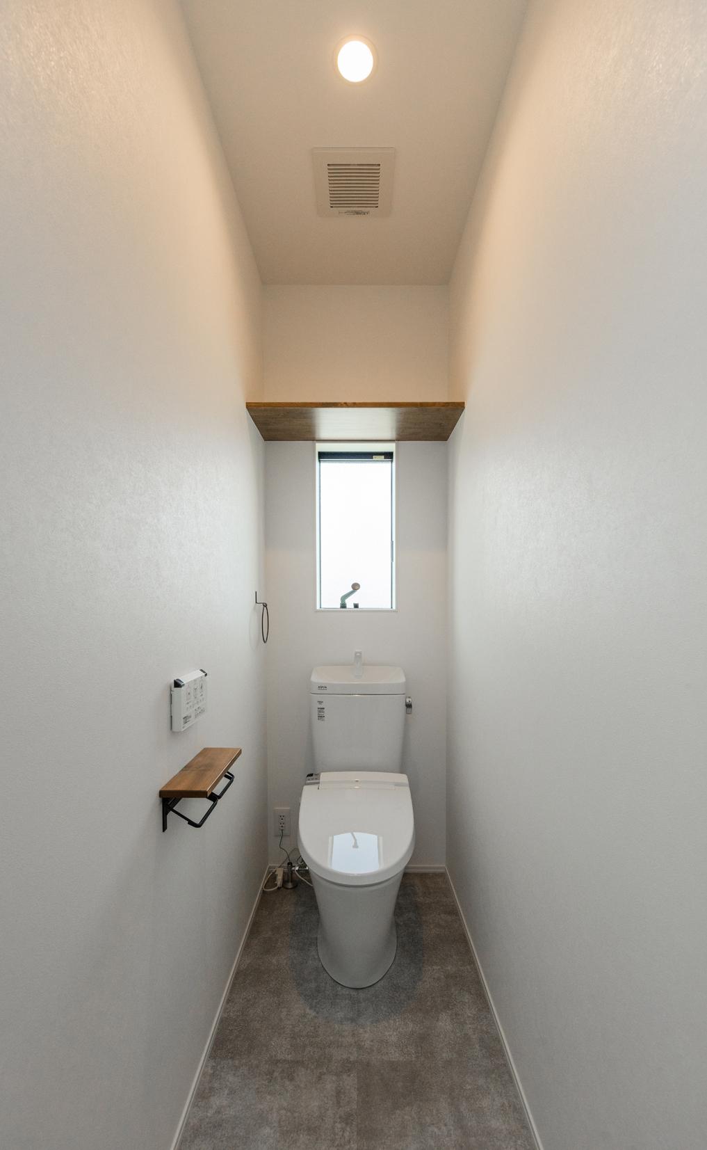 トイレは白を基調にモルタル風の床と無垢材を組み合わせ、シンプルにデザイン