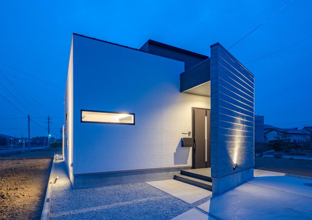 i.u.建築企画【デザイン住宅、間取り、建築家】主要道路沿いのファサードはプライバシーに配慮し、開口部を最小限に抑えてデザイン。玄関ポーチも塀で隠してある。塀は斜めに設けて変化をもたせ、外壁には平形スレートを採用。スポットライトに照らされて、スレートのざらりとした素材感が個性を際立たせている