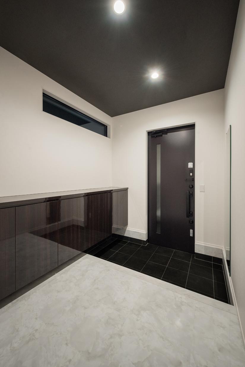 i.u.建築企画【デザイン住宅、間取り、建築家】モノクロームの空間に、大理石調のフロアタイルでアクセントをつけた玄関。鏡面仕上げの造作収納が高級感を漂わせている