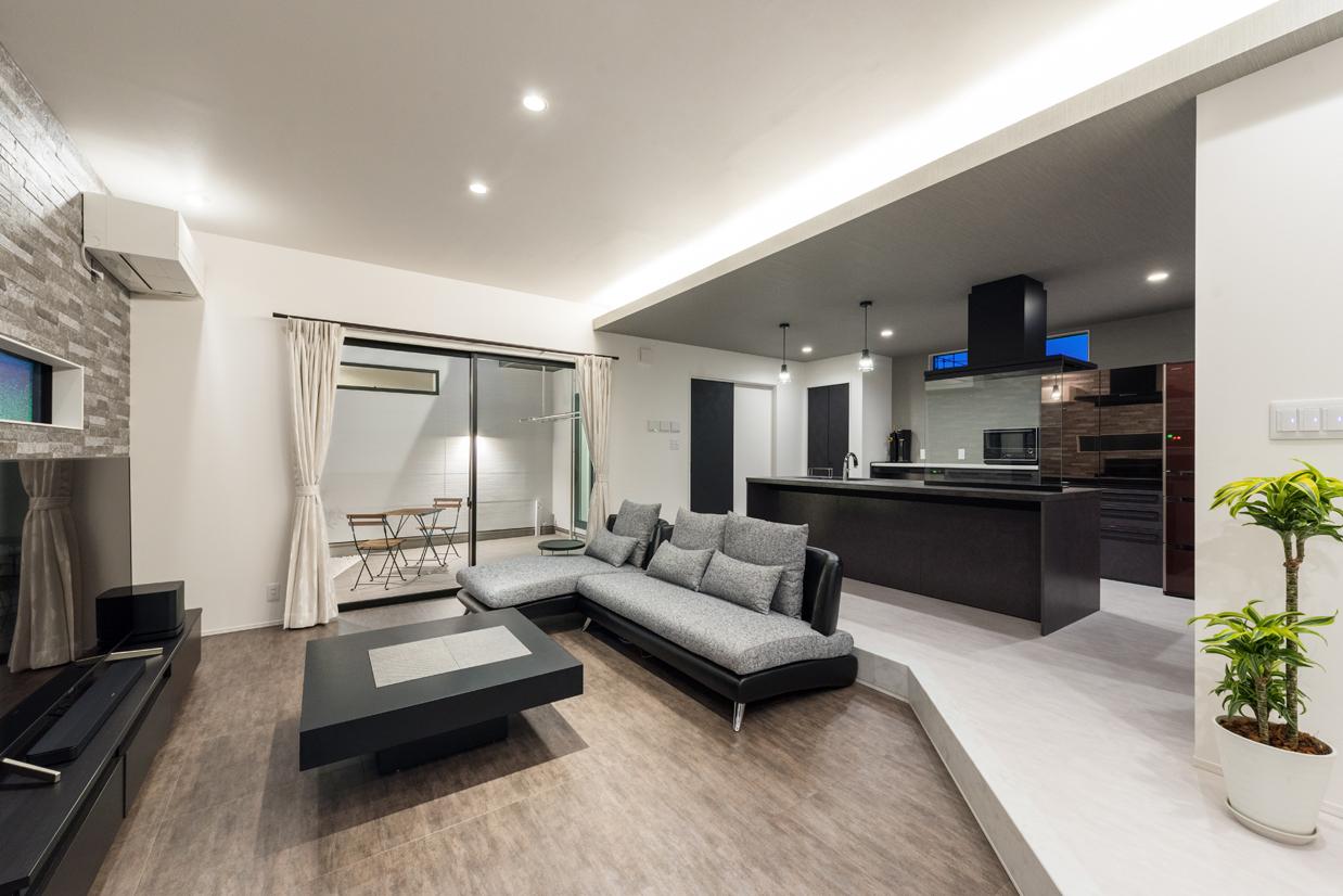 i.u.建築企画【デザイン住宅、間取り、建築家】リビングは床を下げてゾーニングし、落ち着きのあるくつろぎ空間が実現。キッチンはアイランド型にし、回遊できる動線を確保して家事を便利に。掃出窓の外には中庭がある