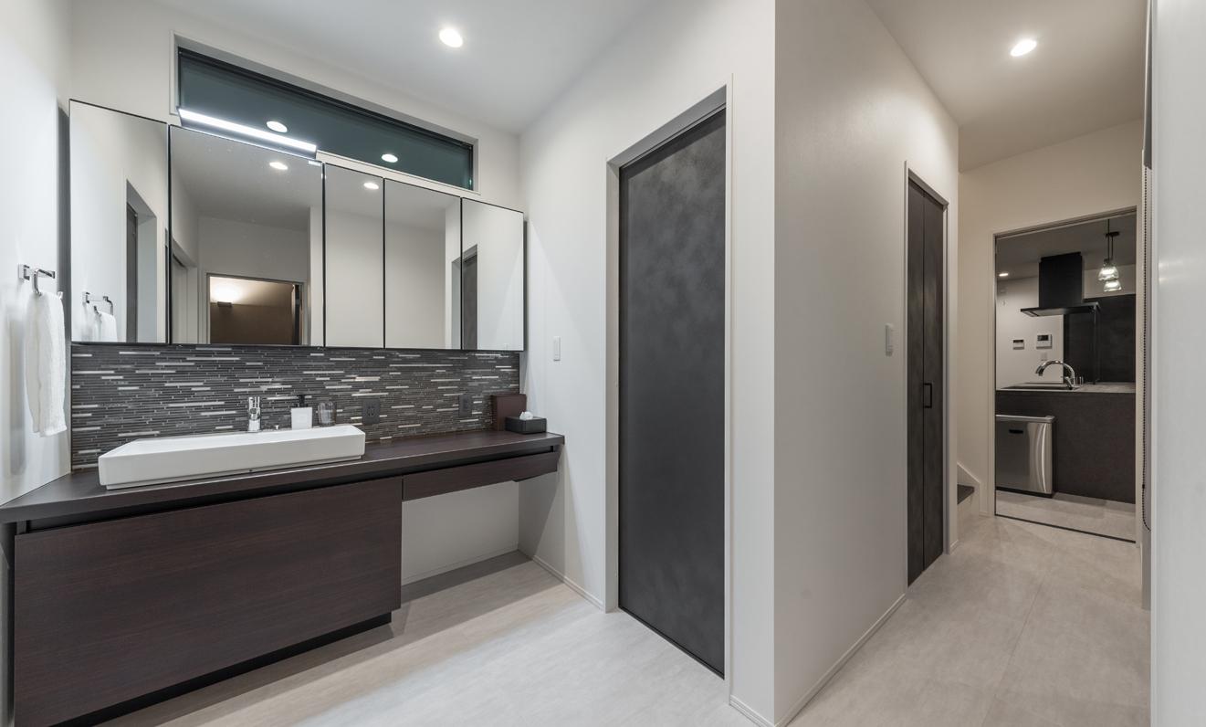 i.u.建築企画【デザイン住宅、間取り、建築家】玄関を上がってすぐ左手に洗面スペースがある。黒いドアの奥はトイレ。廊下の先にLDKが見える