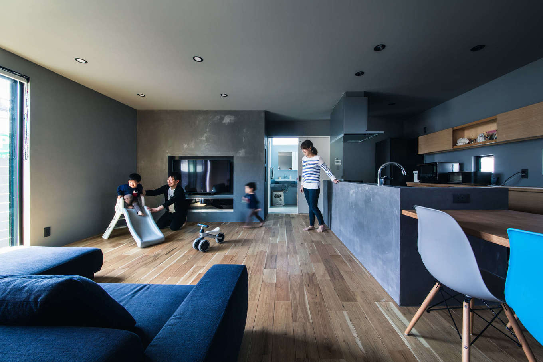 Takukenchiku【デザイン住宅、間取り、インテリア】「もともと持ち物が少ないんです」というTさん。LDKは最低限の家具や家電が並ぶシンプルな空間で、南向きの大きな窓、奥の洗面脱衣室、玄関の吹き抜けの窓から自然光が注がれ、昼は照明が必要ないほど明るい。無垢の床や塗り壁の質感が豊かで、デザイン性とぬくもりが共存