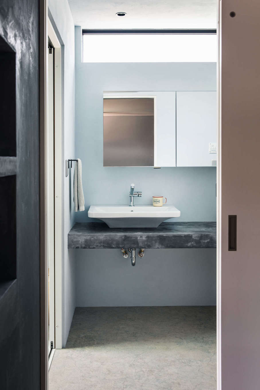 モールテックスで仕上げた造作洗面台に、サンワカンパニーの洗面ボウルを設置。収納付きの大きな洗面鏡は夫妻のお気に入りだ