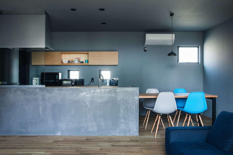 壁付けのキッチンを腰壁で囲み、アイランド風に仕上げたオープンキッチン。モールテックスを塗って仕上げたモルタル調の壁と、アイアンの脚を持つ造作ダイニングテーブル、奥さまが厳選したダイニングチェアが部屋のアクセントに
