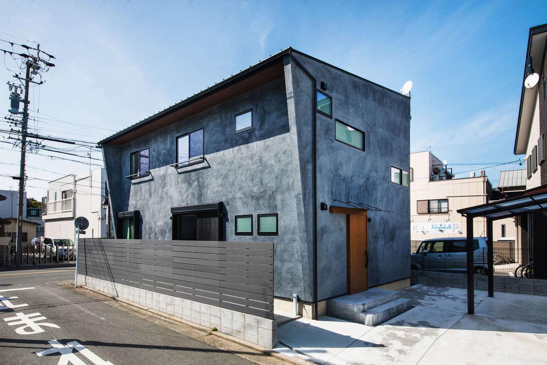 Takukenchiku【デザイン住宅、間取り、インテリア】スタイリッシュな箱型のフォルムと、日光を程よく遮る庇や袖壁が目を引く。あえて濃淡を表現したグレーの塗り壁は、モルタルのような趣きと質感がある。「外構までトータルでプロデュースしてもらえて、統一感ある仕上がりに大満足です」そう夫妻は語る