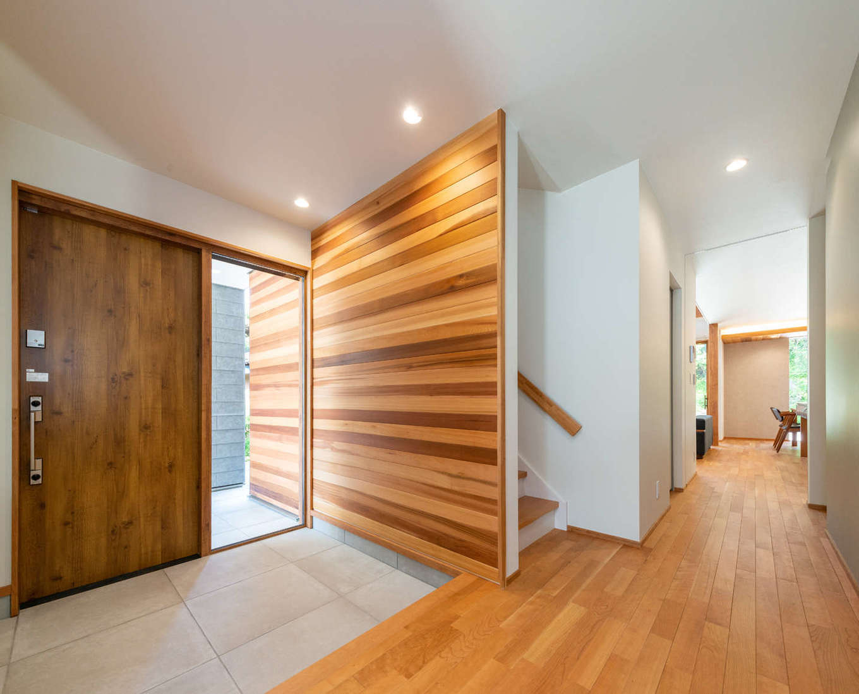 寿鉱業 ナーブの家【デザイン住宅、趣味、間取り】玄関のレッドシダー張りの壁は、透明なガラス窓をはさんで玄関ポーチの壁と繋がっていて、内と外の一体感が強調されている