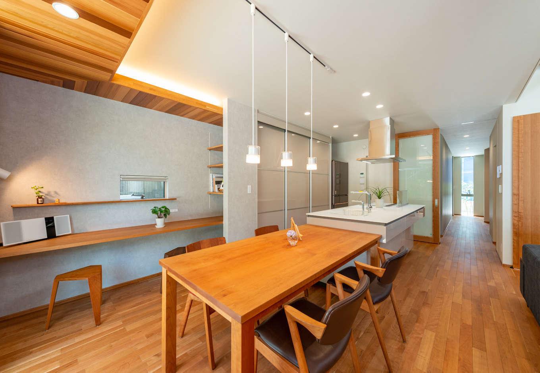 寿鉱業 ナーブの家【デザイン住宅、趣味、間取り】アイランドキッチンとテーブルを一列に並べて配置。背面にはスタディカウンターと収納をたっぷり確保した。キッチンの奥には水回りスペースがあり、動線を一直線に確保して家事ラクを実現。また、水道には汚れを分解する除菌水のシステムを採用している