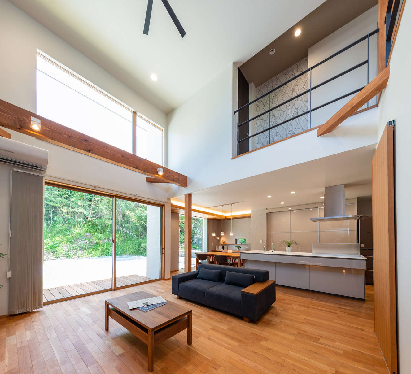 寿鉱業 ナーブの家【デザイン住宅、趣味、間取り】ブラックチェリーの床が心地よさを感じさせるLDK。床暖房を採用し、冬でも足元からぽかぽかの暖かさ。ダイニングキッチンの天井高をあえて低めにしたことで、リビングの吹抜けがいっそうダイナミックで開放的に感じられる