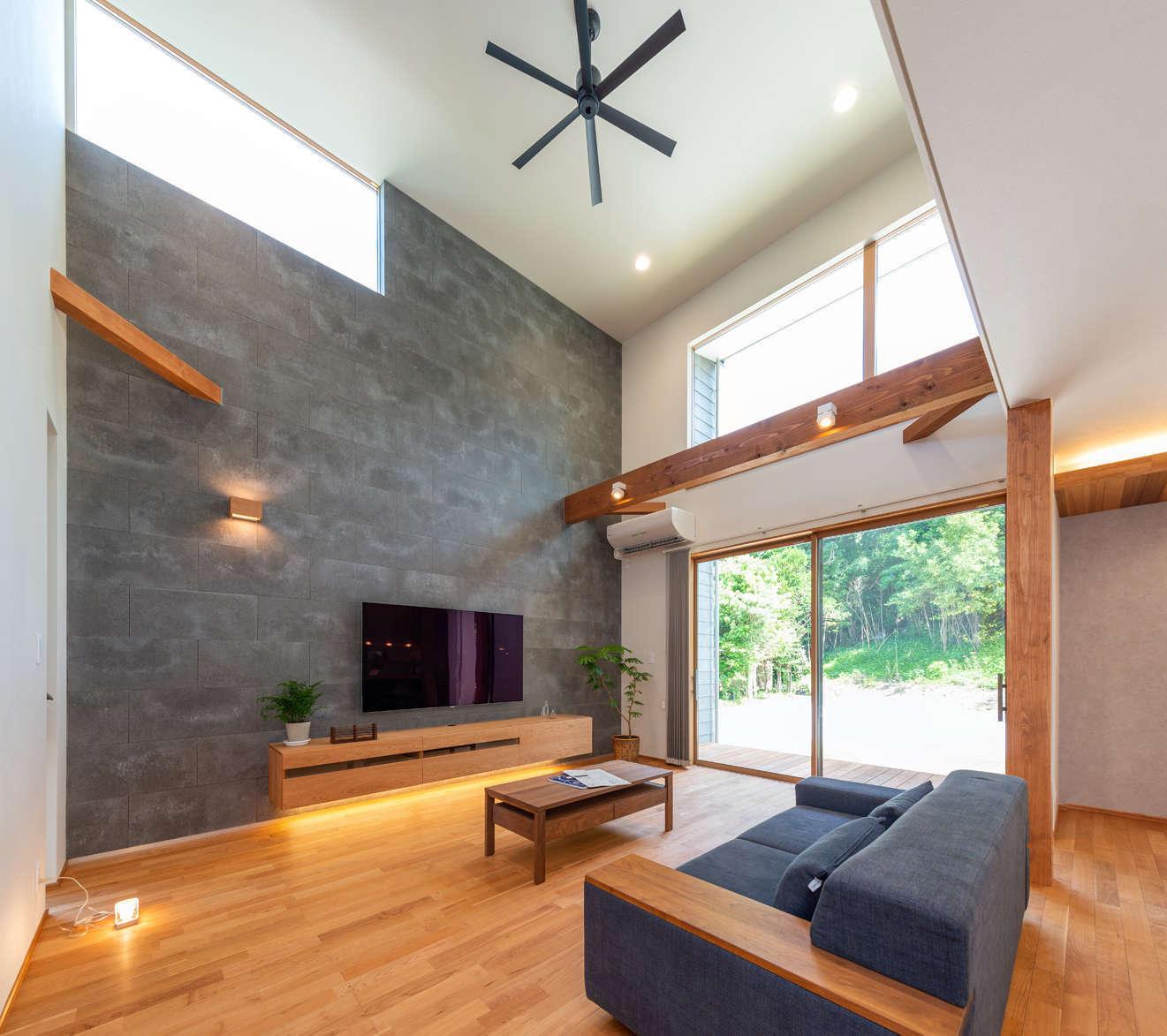 寿鉱業 ナーブの家【デザイン住宅、趣味、間取り】開放感あふれる吹抜けのリビング。大きな掃出窓とハイサイドライトから光をたっぷり採り込み、広い空間全体に明るさをもたらしている。リビングの壁には外壁と同じセメント系天然素材が用いられ、縦空間の広がりを強調しつつ、空間をスタイリッシュに演出