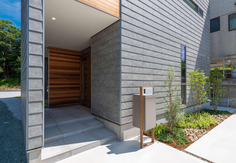 寿鉱業 ナーブの家【デザイン住宅、趣味、間取り】外壁のラップサイディングは天然素材なので1枚1枚表情が異なり、玄関ポーチのレッドシダー張りの壁との相性も抜群。本物の素材が、上質で洗練された雰囲気を醸し出す