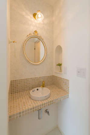 奥さまのセンスを活かしてエレガントに演出した洗面スペース。ベージュのタイルと丸鏡、R型のニッチがベストマッチ