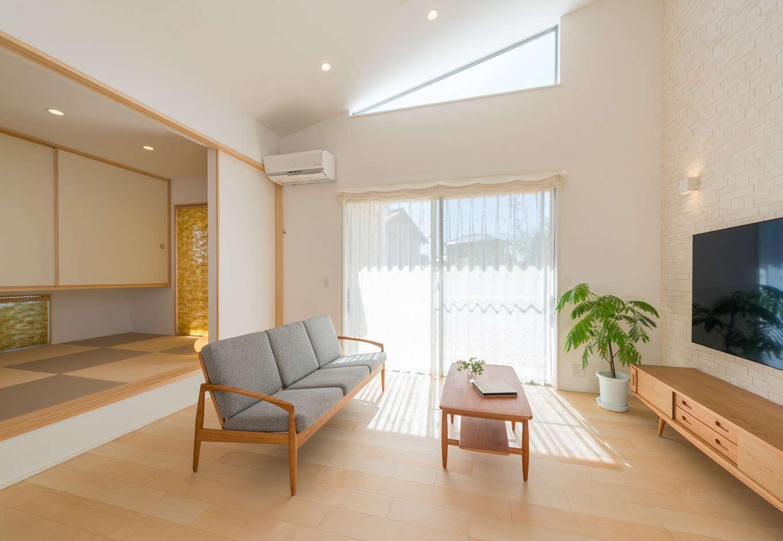 高さ4メートルもの勾配天井が抜群の開放感をもたらすリビング。白と木目を基調にナチュラルで上品な空間にコーディネート。小上がりの畳コーナーは、お子さまの遊び場やお昼寝スペースなど多目的に役立っている