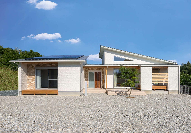 外観は屋根の形に変化を付けて個性を演出。バランスの良いフォルムが緑の風景に映える。建物は中央の玄関を境に、東側にLDK、西側にプライベートルームを配置