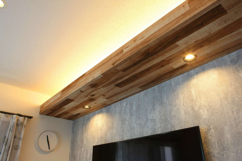 ロイヤルハウス岡崎店(ハート住いる)|テレビの上の梁の上下に間接照明を埋め込み、木目調のクロスを巻いてニュアンスを出した