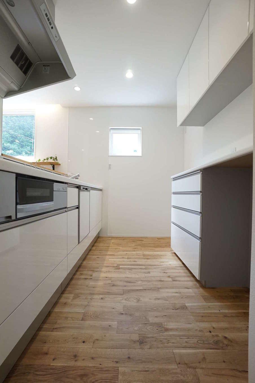 RIKYU (リキュー)【二世帯住宅、間取り、建築家】シンプルで機能的なキッチンは、清潔感ただよう白でコーディネート。バックヤードの収納も充実