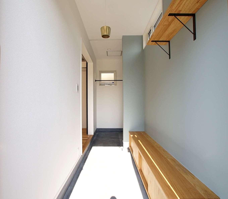 RIKYU (リキュー)【収納力、間取り、建築家】たくさんの靴やキャンプ用品などをしまえる土間収納付き玄関。壁一面に貼ったアクセントクロスと同じ色のクロスやタイルを家中の至る所に使用した