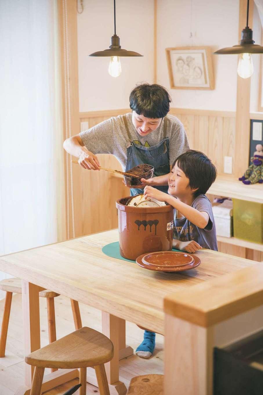 住まい工房 整建【デザイン住宅、和風、間取り】ダイニングで自家製味噌を容器に取り分ける奥さま。お子さまも一緒にお手伝い。テーブルも『整建』のオリジナル