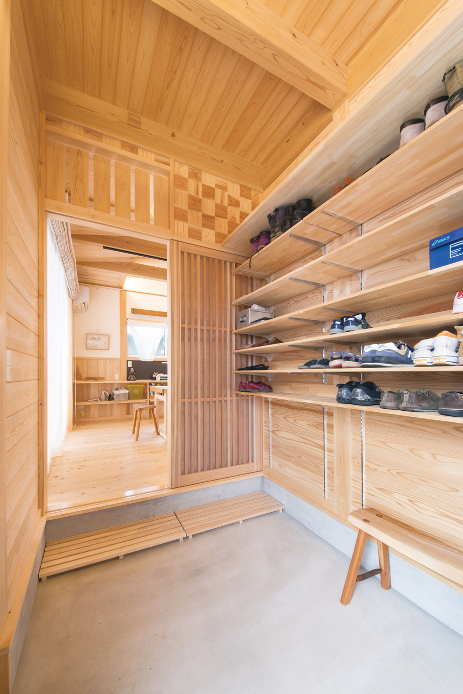 住まい工房 整建【デザイン住宅、和風、間取り】広々とした土間のスペースを確保した玄関。 壁には造作した大容量の収納棚があり、家族の靴もたくさん並んでいる