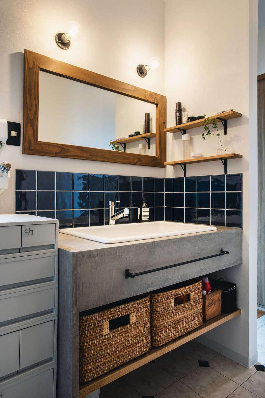 造作の洗面台はモルタルのような質感で、防水性の高いMORART(モラート)を採用。マットな仕上げの中に微妙な光沢感を持ち、柔らかい陰影による奥行きのある表情を演出する。1日1工程で、4日間かけて製作した。ワイドな鏡、ダークブルーのタイル、アイアンの取っ手とのバランスが美しい
