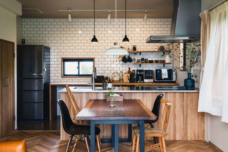 カフェスタイルのオープンキッチン。奥さまのたっての希望で、バックヤードにサブウェイタイルを採用。ペンダントライトはルイス・ポールセン。レンジフードが付いていた垂れ壁を撤去したことで開放感が生まれた。ワークトップ、冷蔵庫、ダッシュBOXをステンレス製にして統一感を出した
