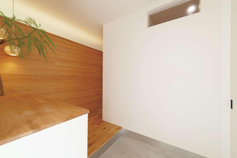 スタイリッシュな土間仕立ての玄関。壁上部の間接照明がやわらかく迎えてくれる