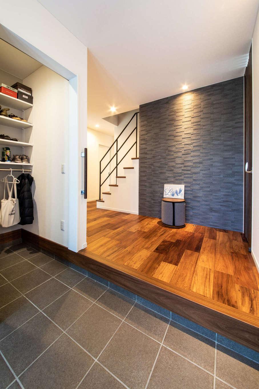 褐色の濃淡が美しいアカシアの床と装飾タイルがオシャレな玄関。階段の裏側に水回りや収納を配置し、回遊動線でつなげている