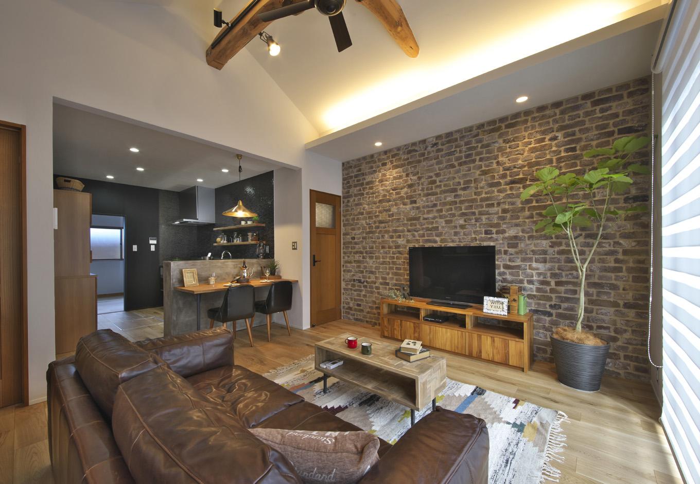 あすなろ設計事務所|勾配天井の開放感に、丸太梁とアクセントのレンガによって適度なぬくもりがブレンドされ、居心地のいいLDKに仕上がった。貼り分けられた壁の素材や天井の高さによって、穏やかに役割が分割されている