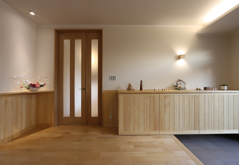KOZEN-STYLE コバヤシホーム【和風、二世帯住宅、平屋】シンプルな木の空間に、間接照明やスポットライトによる灯りの演出を加えて上品に演出した玄関。玄関収納は腰板と同材のパイン材を用いた造作家具。サイドにはお母さまの要望でスリッパをしまう棚を設けてある