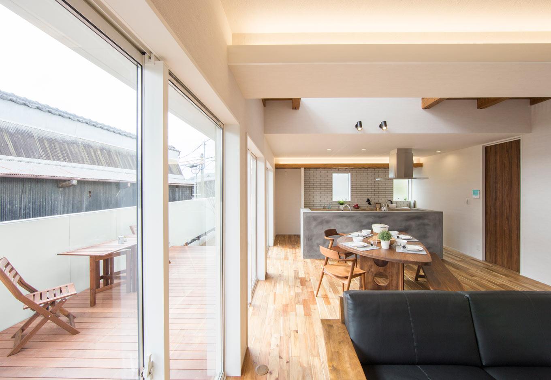 KOZEN-STYLE コバヤシホーム【デザイン住宅、自然素材、省エネ】吹抜けのあるLDK。アカシアの無垢の床材が素足に心地よい。掃出し窓を開け放つと、外のアウターリビングと一体化して35畳もの大空間に。限られた敷地内で抜群の開放感を味わえる