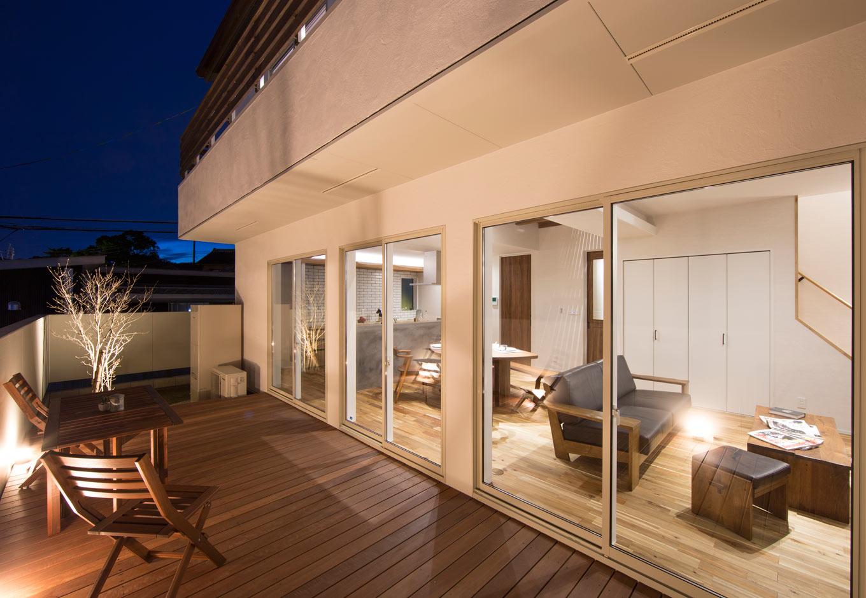 KOZEN-STYLE コバヤシホーム【デザイン住宅、自然素材、省エネ】夜のアウトドアリビング。掃出し窓を開け放てばLDKと一体化して、圧倒的な開放感を味わえる。LDKの南面にこれほどの大開口を集中的に確保できたのは、高強度を誇る「SE構法」ならではの技術