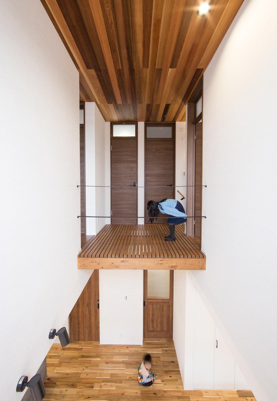 KOZEN-STYLE コバヤシホーム【デザイン住宅、自然素材、省エネ】吹抜けの縦空間。正面の2階の廊下は床をスノコ上にし、手すりとしてアイアンを2本渡して、採光と風通し、開放感に配慮。2階に並んだハイドアの奥は、トイレとウォークインクローゼット。ドアは欄間つきで、こちらも採光と風通しに配慮した