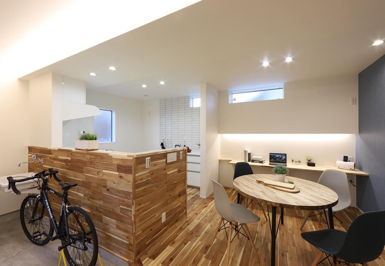 土間に面した対面式のオープンキッチン。腰壁には床と同じアカシア材を張ってある。丸いダイニングテーブルは『KOZEN STYLE』のオリジナル造作家具