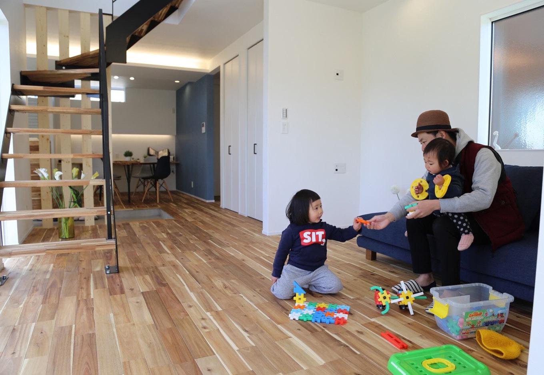広々としたリビングで、子どもと戯れるひととき。土間の向こう側のキッチンから、奥さまが家族の様子を見守れる