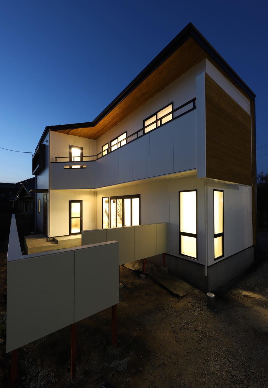夜の外観。敷地を最大限に活かすため、建物をL字型に。土間のテラスドアとリビングの掃出し窓の2方向から庭に出られるので、BBQや庭遊びの際にも便利