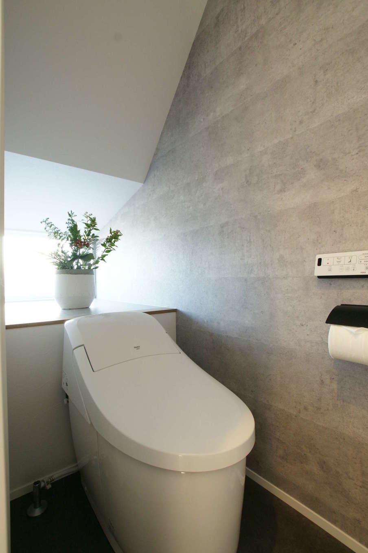 RIKYU (リキュー)【夫婦で暮らす、間取り、建築家】階段下のデッドスペースを活かしてつくったおしゃれなトイレ。無機質なデザインクロス、窓から差し込む淡い光の陰影美が美しい