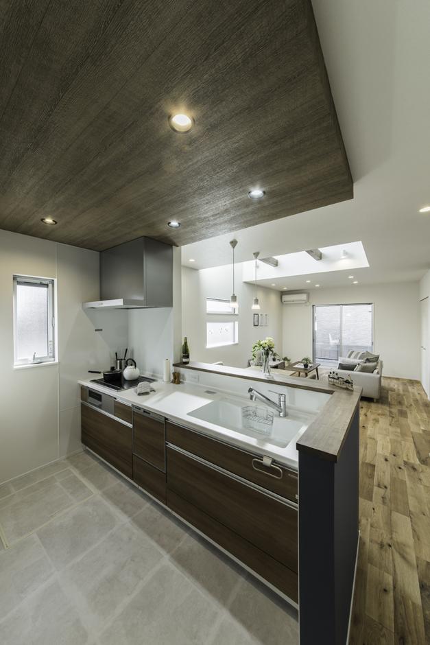 カナルホーム【1000万円台、デザイン住宅、夫婦で暮らす】家族の様子を見渡せる場所に設けたキッチン。天井を10cm下げたアクセントウォールが空間に変化をもたらす