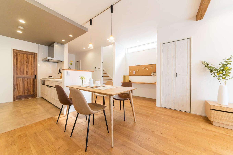 カナルホーム【1000万円台、デザイン住宅、収納力】ダイニングテーブルをキッチンの横にレイアウトしたことで、奥さまの家事効率もUP。キッチンから見える場所にカウンターを造作し、スタディコーナーに。コルクボード付きで、学校から持ち帰ったプリントなども貼っておける