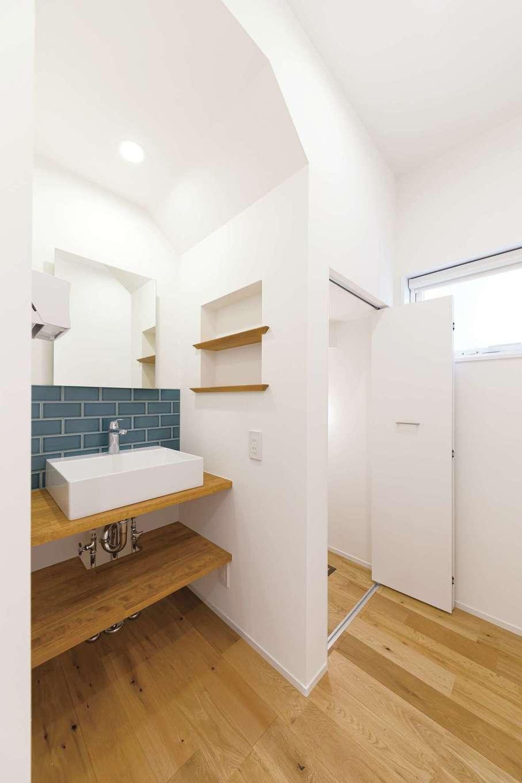 階段下に設けられた洗面は、アーチの壁と緑のタイルがかわいらしいアクセント。右側は階段下収納。デッドスペースも余すことなく活用した