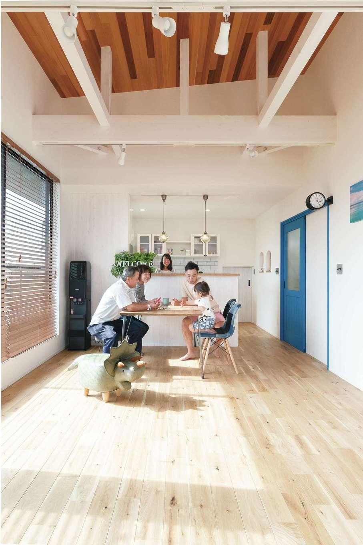小玉建設【デザイン住宅、間取り、スキップフロア】2階の子世帯のLDK。天井に張ったレッドシダーが、部屋全体に温かみをもたらす。2階は部屋ごとにドアの色を変えてあるのが特徴。無塗装のドア材を好きな色にペイントしてもらった。「現場で試し塗りをしてくれたので、イメージが湧きやすかったです」とご主人。リビングのドアはブルーにペイントしてカリフォルニアテイストを演出