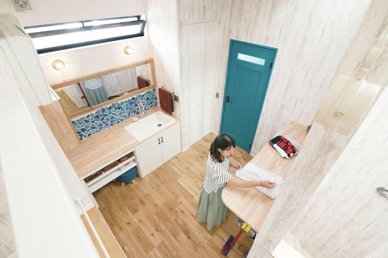 小玉建設【デザイン住宅、間取り、スキップフロア】2階のランドリー。造作の洗面台はクラッシュタイルで差をつけた。家事カウンターの下に室内干しのパイプがある
